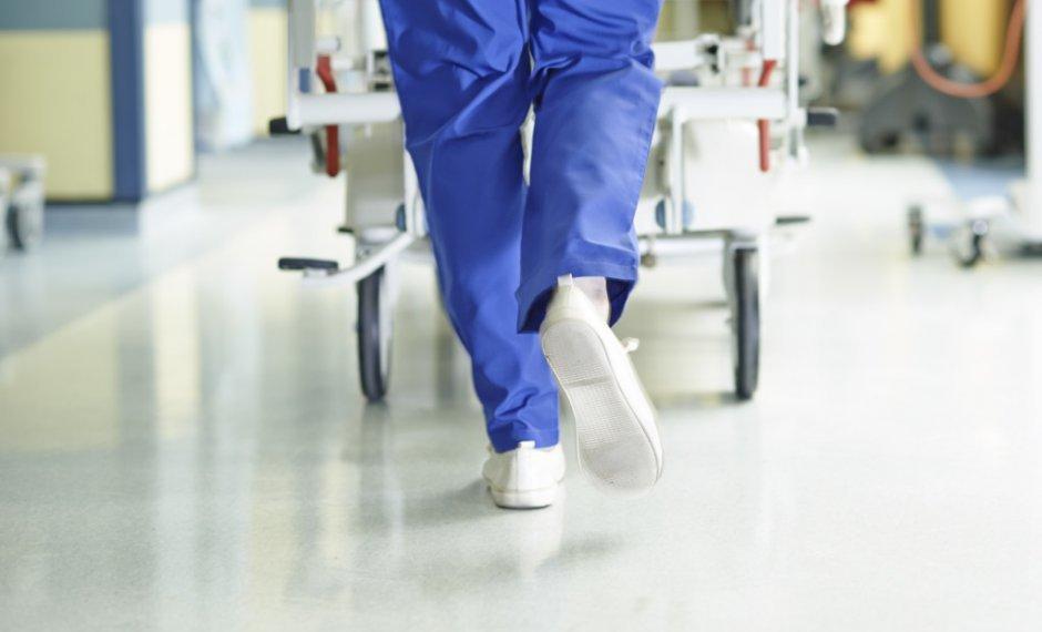 Jambe d'un infirmier devant un lit