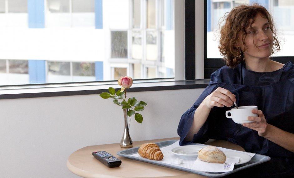 Femme qui mange dans une salle d'hôpital